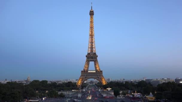 Illuminated Eiffel tower, car pass fast on street, blue  night sky, time lapse