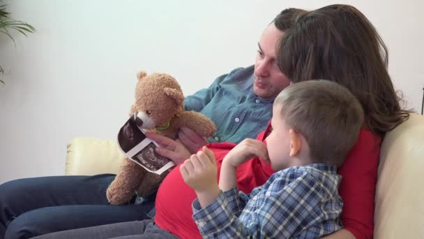 Young father and pregnant mother prepare little child for unborn child coming