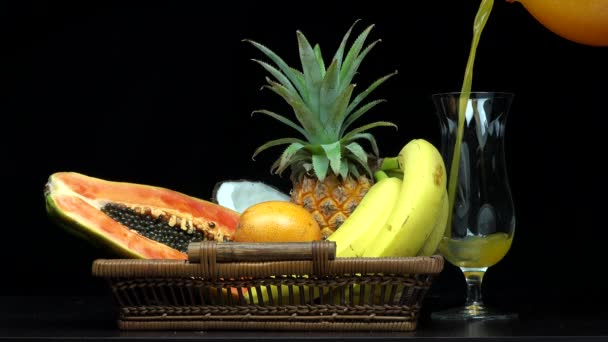 Detail of pouring orange juice in a glass, exotic fruits in a basket