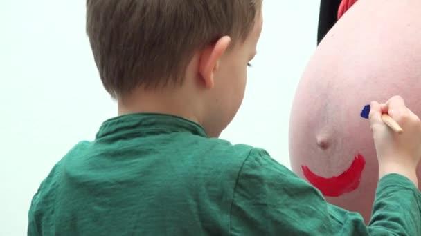 Roztomilé dítě malba břicho těhotné matky, šťastný obličej, hledaný bratr portrét