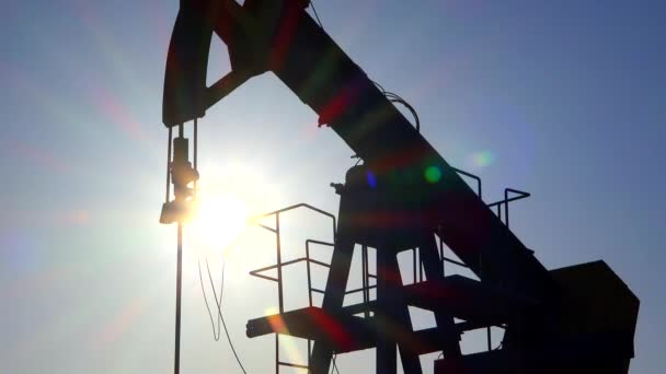 Oil pump fossil fuel extraction hydraulic drilling rig unit silhouette with sun rays in background on industrial platform