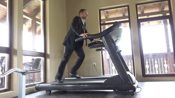 Man with suit running on gym machine, work break, running to succes