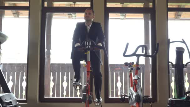 Man with suit training at static bicycle at gym, break at work