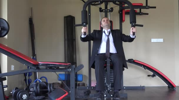 Man wearing suit and tie training with strength machine at gym