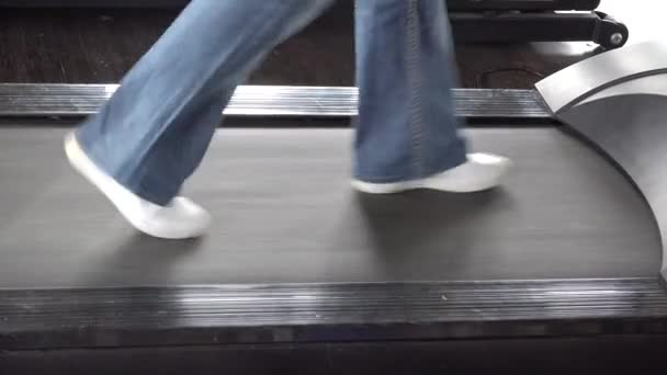 Detail of sportswear feet walking  and running on treadmill at gym