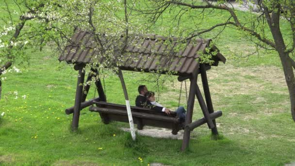 Couple of lovers sit on wooden swing relax and admire green blossom nature, spring love, aerial view