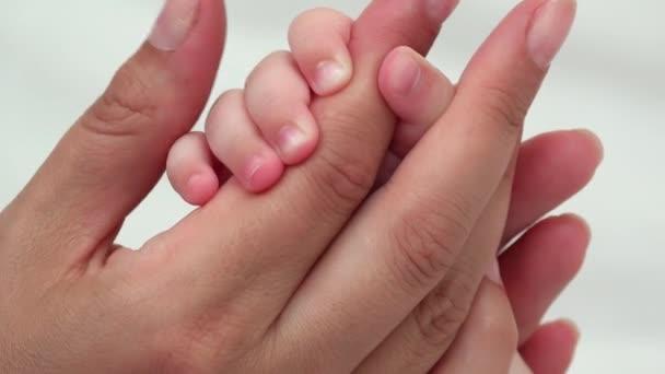 Detailní záběr na baby ruka drží prst, restfully pohlazení