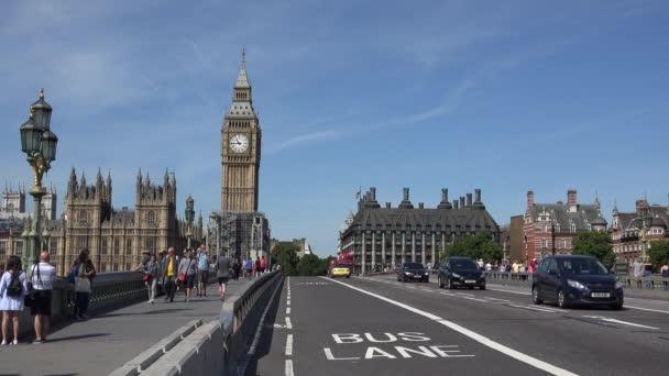 Polgárok, ingázók, turisták, piros emeletes busz és fekete retro taxi taxik, a Westminster Bridge repülőtér közelében, a Big Ben London