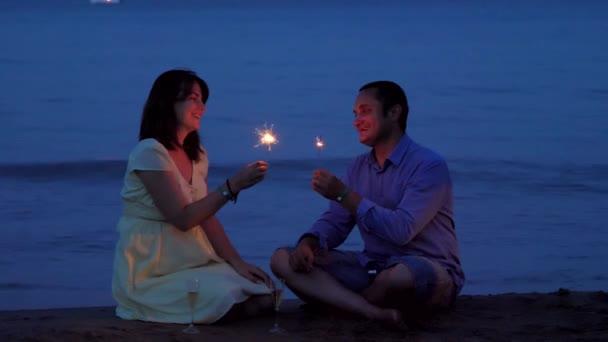 Romantische Liebhaber paar feiern mit Wunderkerzen-Feuerwerk und Champagner am Strand bei Sonnenuntergang