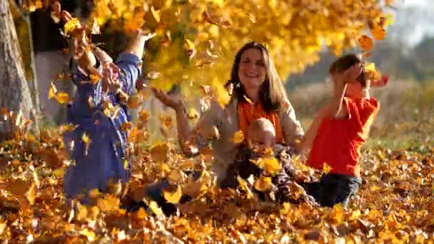 Happy family joy and fun in nature playing with autumn leaves, slow motion