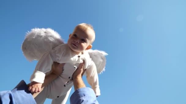 Malé roztomilé dítě s bílými andělskými křídly paintballovém v nadřazeném ruce na modré obloze