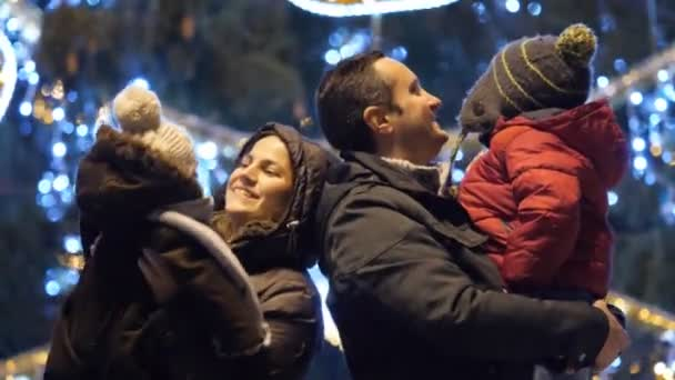 Young parents and baby dancing in front of Christmas tree in city center