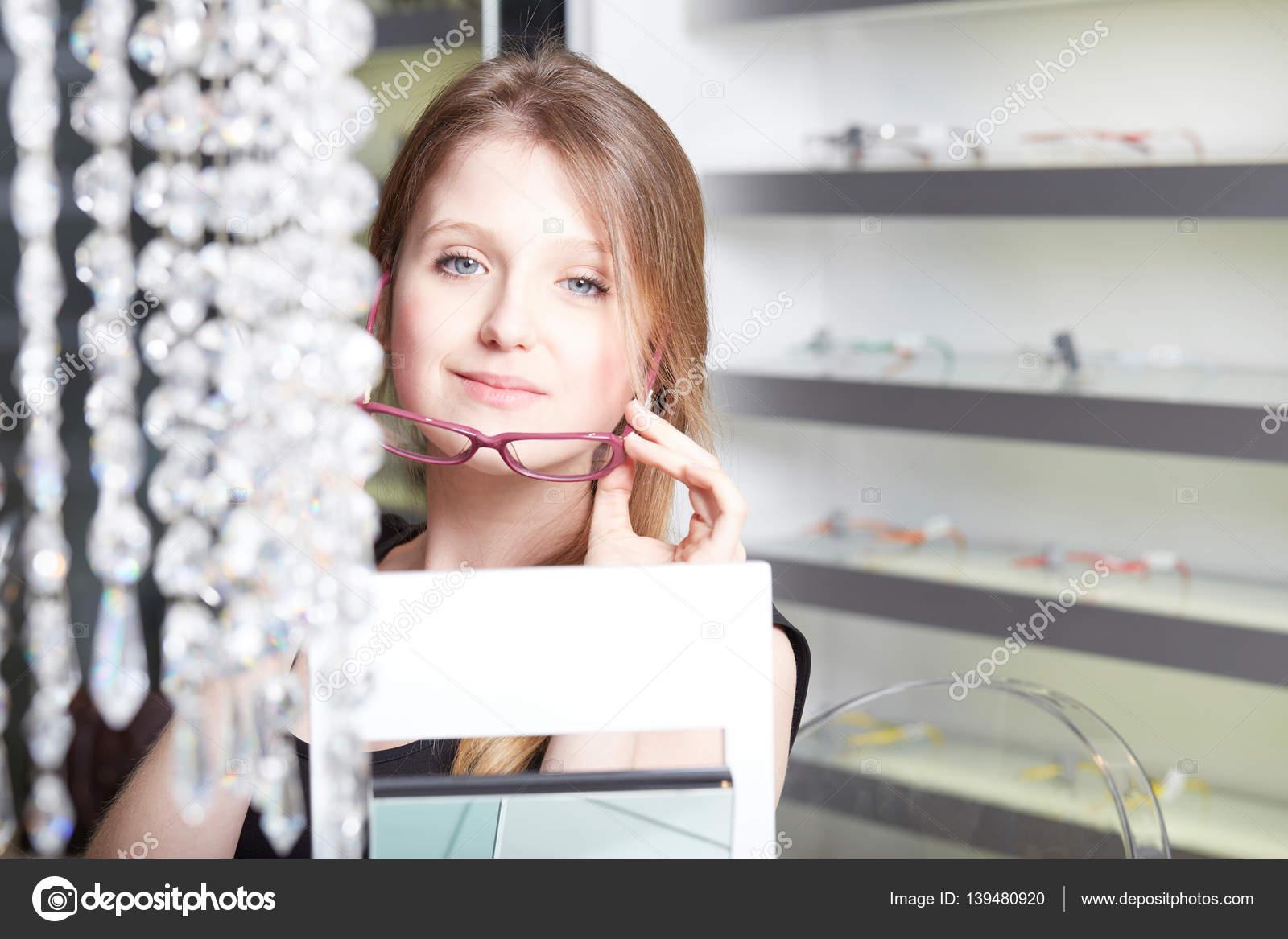 Mujer bonita, joven, elegir nuevos marcos de gafas en una tienda de ...