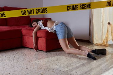 Crime scene imitation. Lifeless woman lying on the sofa