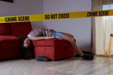 Crime scene imitation. Lifeless woman lying on the sofa