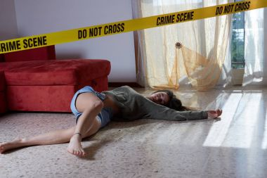 Crime scene imitation. Lifeless woman lying on the floor