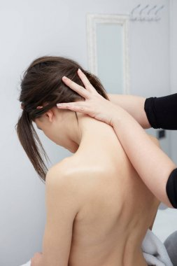 Woman enjoying a wellness back massage in a spa, she is very relaxed