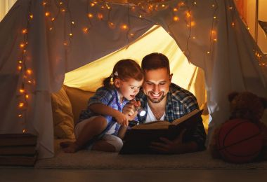 Happy family father and child daughter reading a book  in  tent
