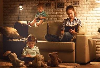 Family before going to bed mother and children read books and pl