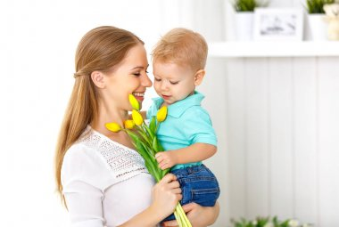 Happy mother's day. Baby son gives flowers for mom