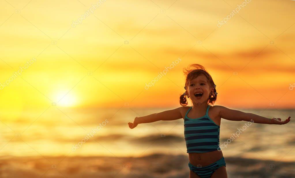 Happy child girl in bikini on beach in summer sea