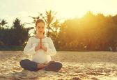 Fotografie Frau praktiziert Yoga und meditiert im Lotussitz am Strand