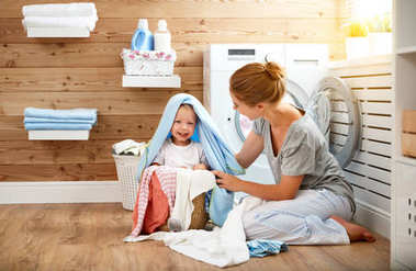 Happy family mother   housewife and children in   laundry load w