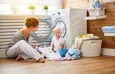 Happy family mother  housewife and children in the laundry load washing machine