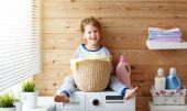 glückliche kleine lustige Hausfrau Baby Mädchen in Waschküche mit Waschmaschine