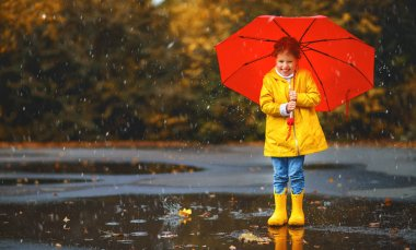 happy child girl with an umbrella and rubber boots in puddle  on