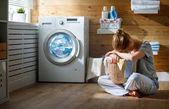 Fotografie müde Hausfrau Frau in Stress schläft im Waschraum mit Wasch-