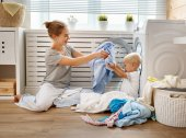 Happy family mother   housewife and   baby son in   laundry load