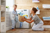 Happy family mother housewife and child   in laundry with washin