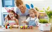 Happy easter! family mother and children paint eggs for   holida