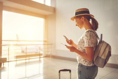 young woman waiting for flying at airport at window with suitcas