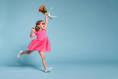 funny child girl runs and jumps with bouquet of flowers on a colored backgroun