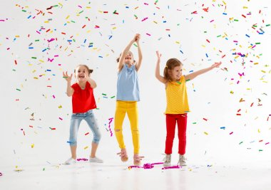 happy children on holidays  jumping in multicolored confetti on