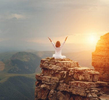 woman practices yoga and meditates   on mountains