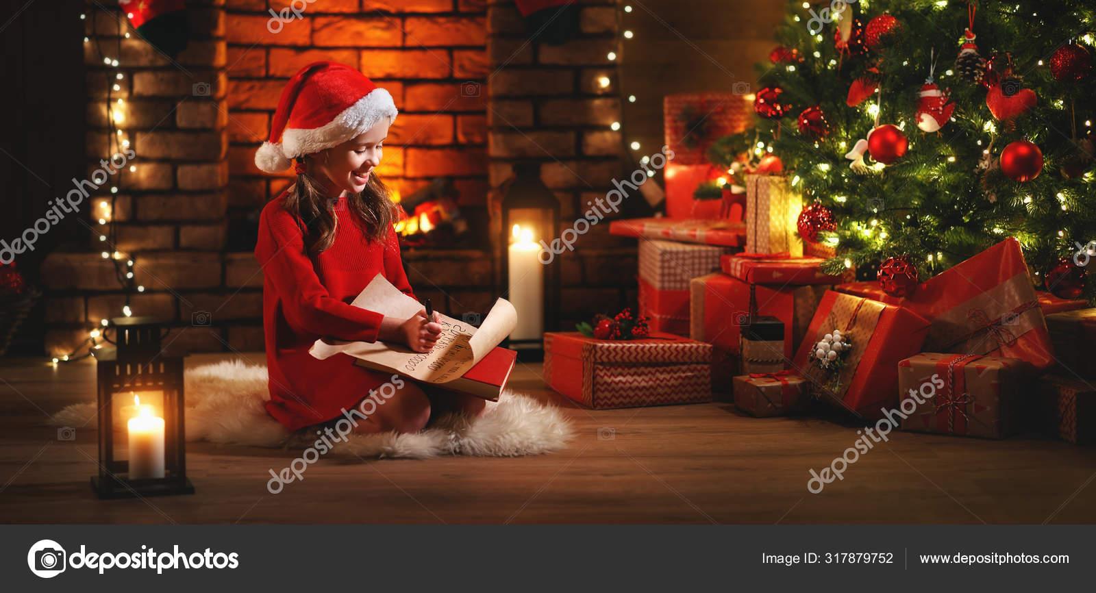 Happy child girl writing letter santa home near Christmas tre — Stock Photo