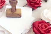 empty paper and wooden stamp decorated with rose flowers