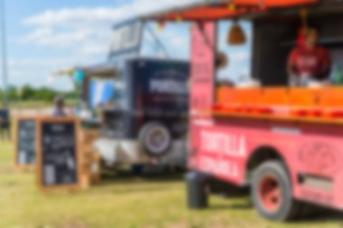 Food trucks and people at a street food market festival, blurred on purpose.