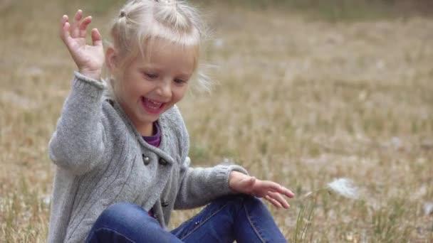 Lány gyermek fúj bolyhos bolyhos