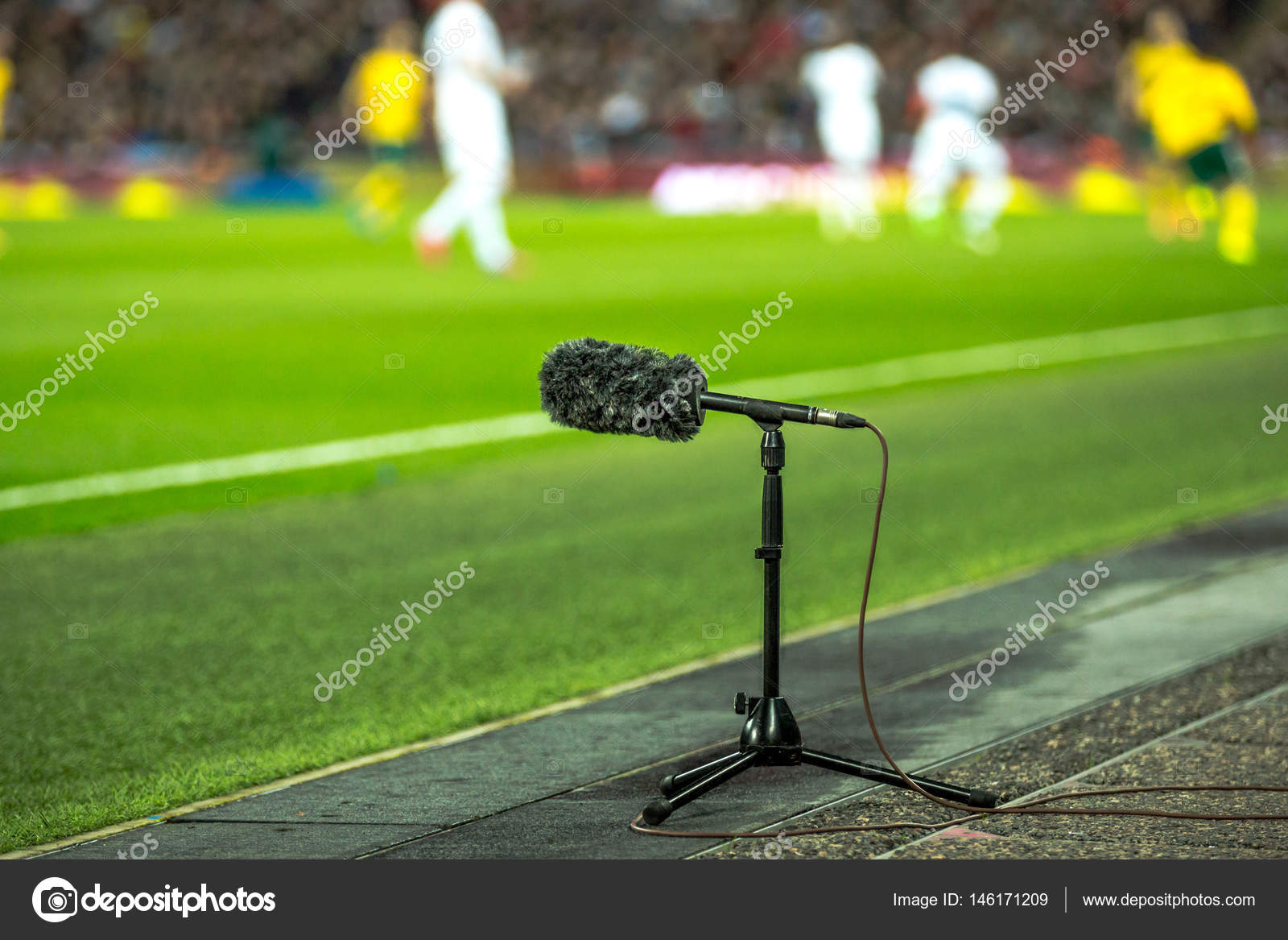 11eacc071 Professional sport microphone on a football field with players training in  the background — Stock Photo