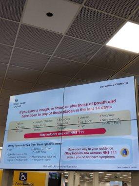 01/03/2020 - Luton Airport, United Kingdom - Coronavirus warning/alert screen in the arrival hall.