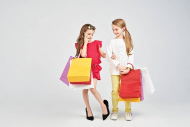 Two pretty girls are standing at the studio. One of them has over-size shoes and calling someone. Two best friends are holding shoppers bags. Shopping, purchases, buy concept stock vector