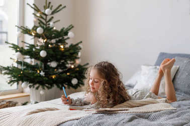 Horizontal shot of restful small female child with long curly hair looks attentively at sheet of paper, colors different pictures, lies on bed near decorated Christmas tree, expectes coming holidays.