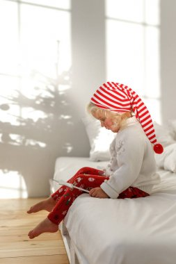 Little blonde child in Christmas hat sits on bed with white bedclothes, plays with magic wand, has serious concentrated expression, thinks about something majestic or miracle. Childhood concept