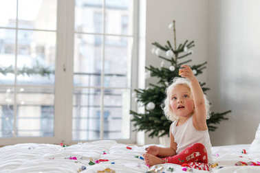 Children, Christmas and New Year concept. Adorable blonde female child wears pyjamas, plays with colourful confetti on comfortable bed, enjoys winter and holidays, decorated fir tree in background.