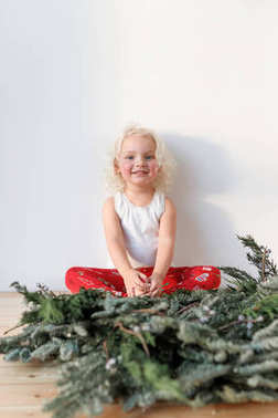 Vertical shot of cute lovely small girl sits crossed legs against white background, has happy expression, rejoices coming winter holidays, has appealing appearance, green garland in foreground