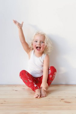 Adorable small female child wears pyjamas, sits on wooden floor raises hands as happy to see affectionate parents, isolated over white background. Cheerful cute smiling little kid indoor at home.